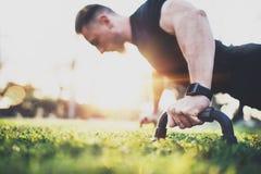 Treningu stylu życia pojęcie Mięśniowy atlety ćwiczyć pcha up outside w pogodnym parku Dysponowany bez koszuli męski sprawność fi Zdjęcie Royalty Free
