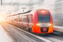 Treno ad alta velocità con i fari luminosi e giri all'alta velocità alla stazione ferroviaria nella città Immagine Stock Libera da Diritti