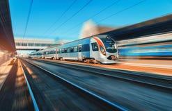 Treno ad alta velocità nel moto alla stazione ferroviaria al tramonto Fotografia Stock