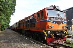Treno arancio sull'attesa della stazione ferroviaria Immagine Stock Libera da Diritti