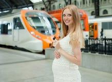 Treno in attesa sorridente della donna incinta Fotografia Stock