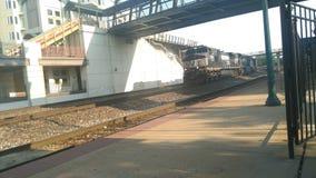 Treno che va sotto il ponte pedonale Immagine Stock