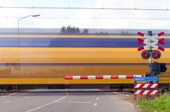 Treno con moto al passaggio a livello Immagine Stock