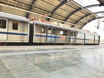Treno della metropolitana di Delhi ad una stazione della metropolitana più di meno ammucchiata a Nuova Delhi nel tempo di mezzogi immagine stock libera da diritti