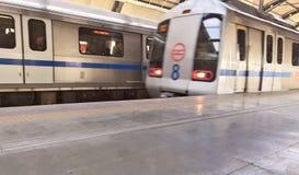 Treno della metropolitana di Delhi ad una stazione della metropolitana più di meno ammucchiata a Nuova Delhi nel tempo di mezzogi fotografia stock libera da diritti