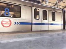 Treno della metropolitana di Delhi ad una stazione della metropolitana più di meno ammucchiata a Nuova Delhi nel tempo di mezzogi fotografie stock libere da diritti