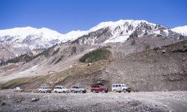 Treno delle automobili sulla strada di avventura fra la montagna della neve Immagine Stock Libera da Diritti
