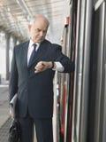Treno di Checking Time By dell'uomo d'affari nella stazione Immagini Stock