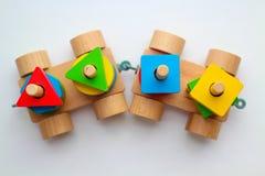 Treno di legno di vista superiore sui precedenti bianchi I dettagli variopinti del giocattolo attirano l'attenzione del bambino fotografia stock