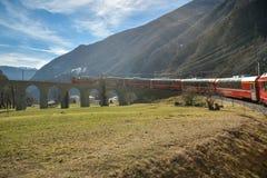 Treno espresso di Bernina che guida giù il viadotto a spirale famoso di Brusio immagini stock