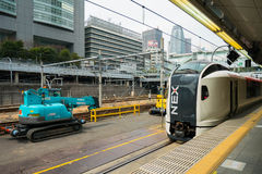 Treno espresso di Narita alla stazione di Shinjuku con il backg della torre del bozzolo Fotografie Stock Libere da Diritti