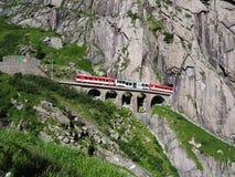 Treno espresso rosso sul ponte ferroviario della st Gotthard e sul tunnel pietrosi scenici, alpi svizzere, SVIZZERA Fotografie Stock