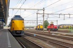 Treno giallo al binario della stazione ferroviaria Immagini Stock