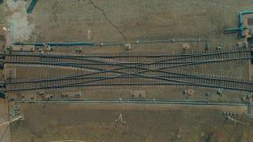 Treno luminoso di colore che passa le rotaie, vista superiore Volo sopra i binari ferroviari archivi video