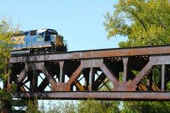 Treno merci che attraversa un ponte d'acciaio del fiume della capriata della ferrovia Immagini Stock