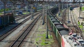 Treno merci con carbone che passa stazione ferroviaria stock footage
