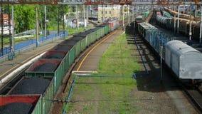 Treno merci con carbone che passa stazione ferroviaria video d archivio