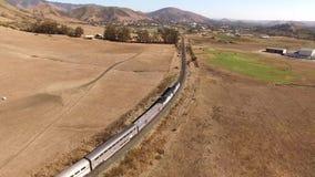 Treno passeggeri urbano moderno enorme che si muove attraverso il deserto asciutto della collina del canyon della steppa della sa archivi video
