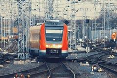 Treno pendolare arancio moderno su una ferrovia Fotografie Stock Libere da Diritti