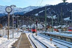 Treno rosso brillante che arriva allo stati della ferrovia di Garmisch-Partenkirchen Immagini Stock