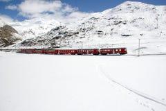 Treno rosso che attraversa through il paesaggio di inverno nelle alpi svizzere vicino a St Moritz Immagini Stock Libere da Diritti