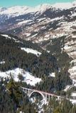 Treno rosso che attraversa un ponte nelle alpi svizzere Fotografia Stock