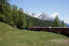 Treno rosso che scala lentamente al passaggio di Bernina nelle alpi svizzere Fotografie Stock