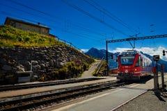Treno rosso di RhB nella stazione ferroviaria di Alp Grum, Grigioni, Svizzera Fotografia Stock