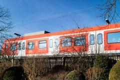 Treno rosso variopinto che attraversa un ponte a arco Fotografia Stock