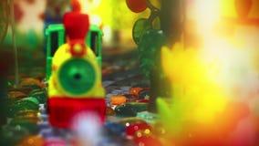 Treno variopinto del giocattolo che si muove dalle rotaie sulla macchina fotografica Ferrovia alta vicina dei bambini stock footage