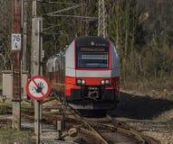 Treno veloce elettrico rosso in montagne delle alpi dell'Austria Fotografie Stock