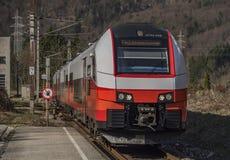 Treno veloce elettrico rosso in montagne delle alpi dell'Austria Fotografia Stock