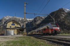 Treno veloce elettrico rosso in montagne delle alpi dell'Austria Fotografia Stock Libera da Diritti