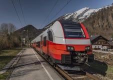 Treno veloce elettrico rosso in montagne delle alpi dell'Austria Fotografie Stock Libere da Diritti