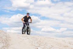 Trenować bicyclist w chalky łupie Brutalny mężczyzna na grubym rowerze zdjęcie stock