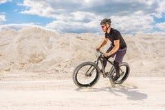 Trenować bicyclist w chalky łupie Brutalny mężczyzna na grubym rowerze zdjęcia stock