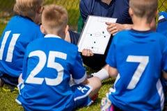 Trenować dzieciak piłkę nożną Drużyna Futbolowa z trenerem przy stadium B zdjęcie royalty free