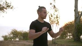 Trenować na świeżym powietrzu Przystojni młody człowiek robi rozciągania ćwiczeniom, rozgrzewkowi w górę ręk i nadgarstków przed  zdjęcie wideo