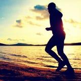 Trenować przy zmierzchem Działający wysoki mężczyzna Sylwetka jogger przy ścieżką wzdłuż jeziornej linii brzegowej Zdjęcie Royalty Free