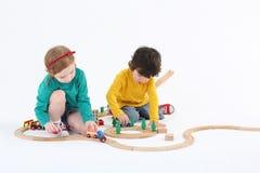 Trens bonitos pequenos do rolo da menina e do menino na estrada de ferro de madeira Imagens de Stock