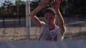 Trens da menina do jogador de voleibol da praia na praia no movimento lento atrás da rede video estoque