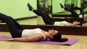 Trens da mulher no gym A mulher encontra-se na esteira e nos músculos abdominais das bombas filme