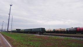 Trens de mercadorias com vagões e reservatórios na estrada de ferro na planta filme