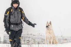 Trens do homem que sentam o cão no inverno na neve fotografia de stock royalty free