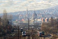 Trens em trilhas de estrada de ferro contra a opinião da cidade de Budapest foto de stock