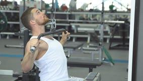 Trens musculares novos do homem no gym Atleta do treinamento do peso filme