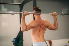 Trens novos de um atleta no gym Mostra os músculos da parte traseira e da caixa imagens de stock