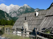 The Trenta Valley Landscape. Old alpine cottages in the Trenta valley with mountains in the background Stock Photography