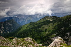 Trenta Valley with storm clouds, Julian Alps, Slovenia. The misty Trenta Valley covered with storm clouds with the green slopes of Zadnjiski Ozebnik peak from Stock Photography