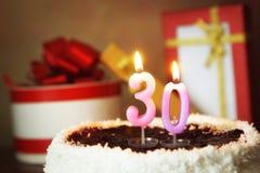 Trente ans d'anniversaire Gâteau avec les bougies et les cadeaux brûlants Photographie stock